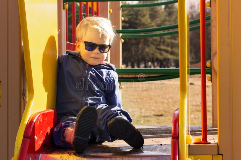Cute baby boy in sunglasses on the playground.  stock images