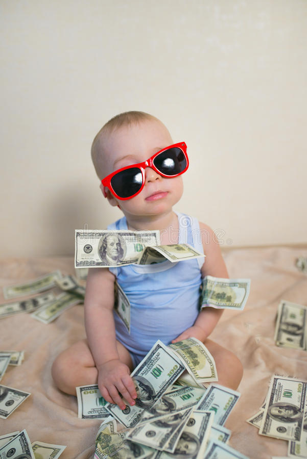 Cute baby boy in sunglasses playing with money, hundreds of dollars.  royalty free stock photos