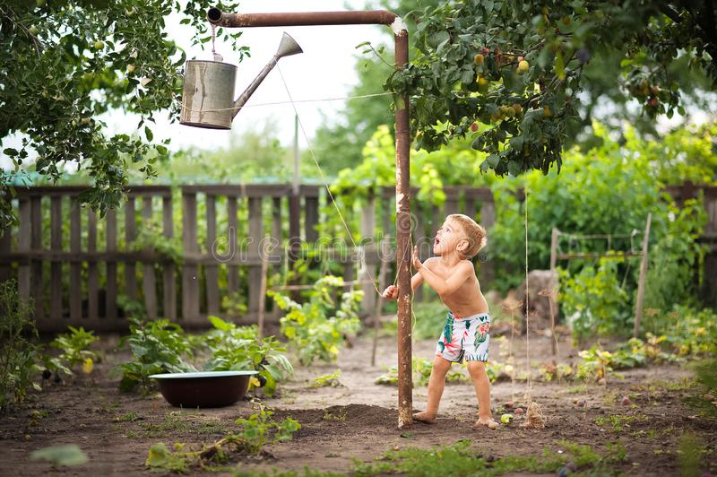 Cute baby boy taking water procedures in summer garden. Outdoor baby bathing. Funny little boy playing with garden hose in sunny b stock photos