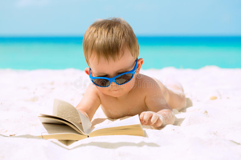 Cute baby boy on vacations. Cute baby boy with sunglasses lying on white sandy beach, reading the book and having his first tropical vacation stock image