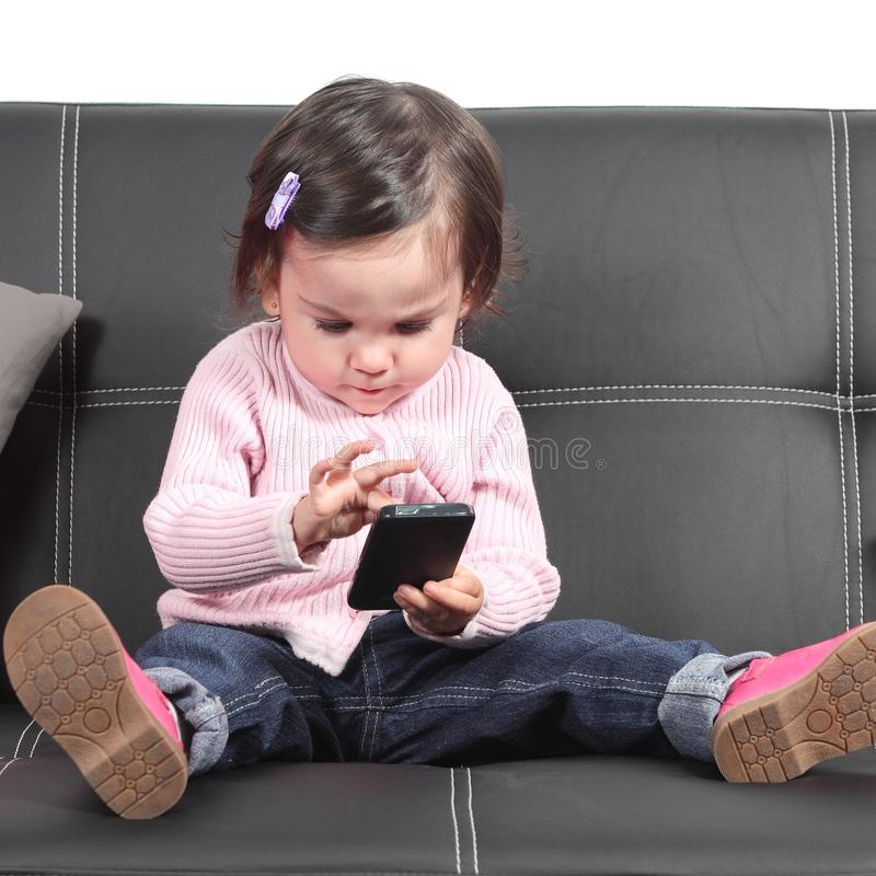 Cute baby browsing in a smartphone. Sitting on a black couch at home