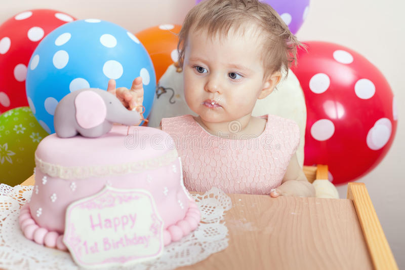 Cute baby celebrating first birthday and eating cake. royalty free stock images