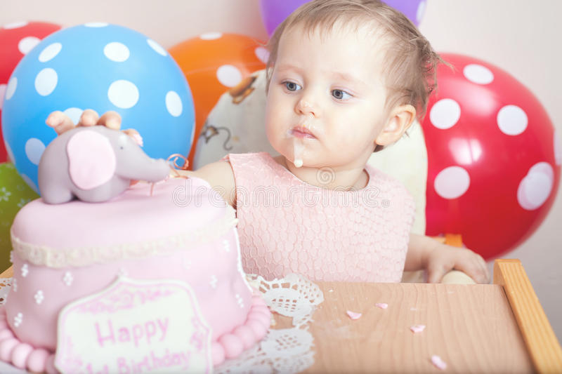 Cute baby celebrating first birthday and eating cake. Cute baby celebrating first birthday - one year and eating cake. Child with many balloons! Make a first royalty free stock images