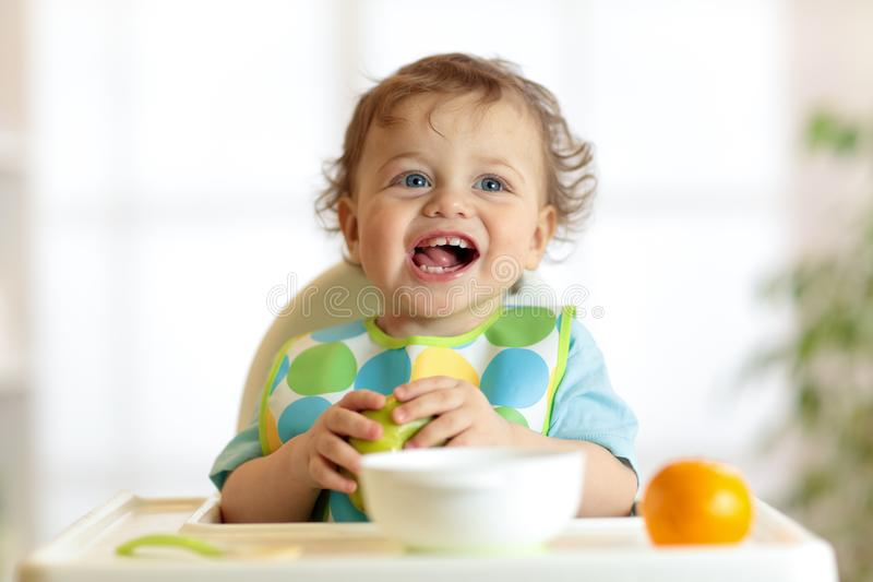 Cute baby child eats healthy food. Portrait of happy kid boy with bib in high chair. royalty free stock photography