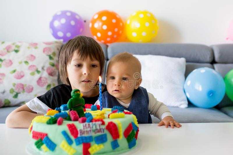 Cute baby child and his older brother, boys, celebrating his first birthday with colorful cake, candles, balloons. Cute children, baby boy and his older brother stock image