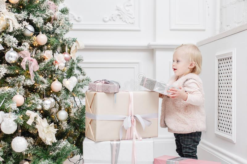 Cute baby and christmas gifts. Little child having fun near Christmas tree in living room. Loving family Merry Christmas. And Happy New Year stock photos