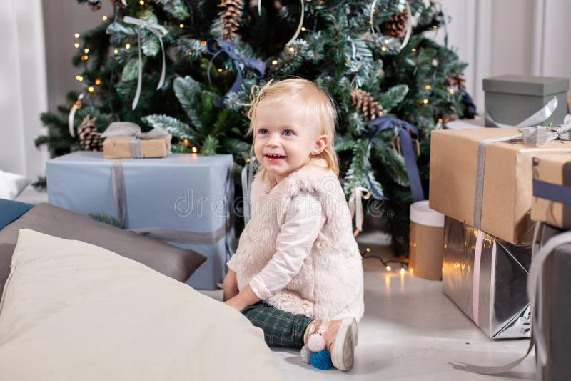 Cute baby and christmas gifts. Little child having fun near Christmas tree in living room. Loving family Merry Christmas. And Happy New Year royalty free stock image