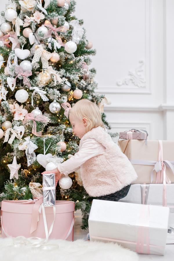 Cute baby and christmas gifts. Little child having fun near Christmas tree in living room. Loving family Merry Christmas. Cute baby and christmas gifts. ttle stock photos