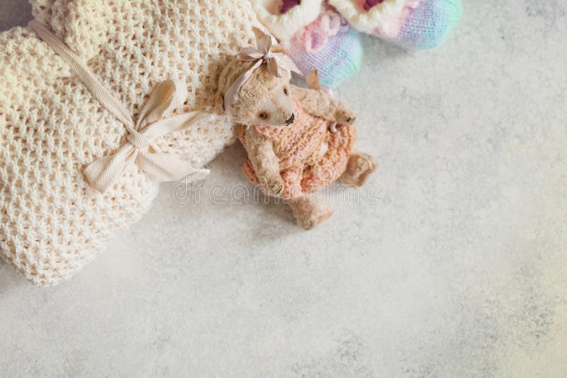 Cute baby clothes for girl. Wowen wrap, booties, teddy bear toy royalty free stock images