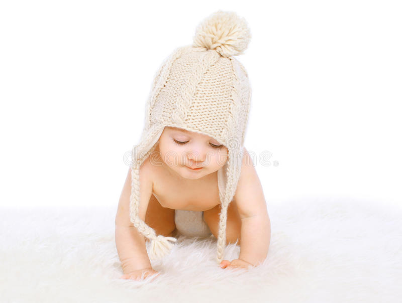 Cute baby in comfort knitted hat crawling royalty free stock photography