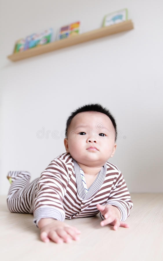 Cute Baby crawling on living room floor stock images