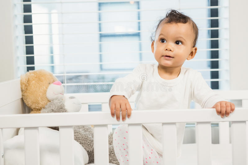Cute baby in the crib. Looking around royalty free stock image
