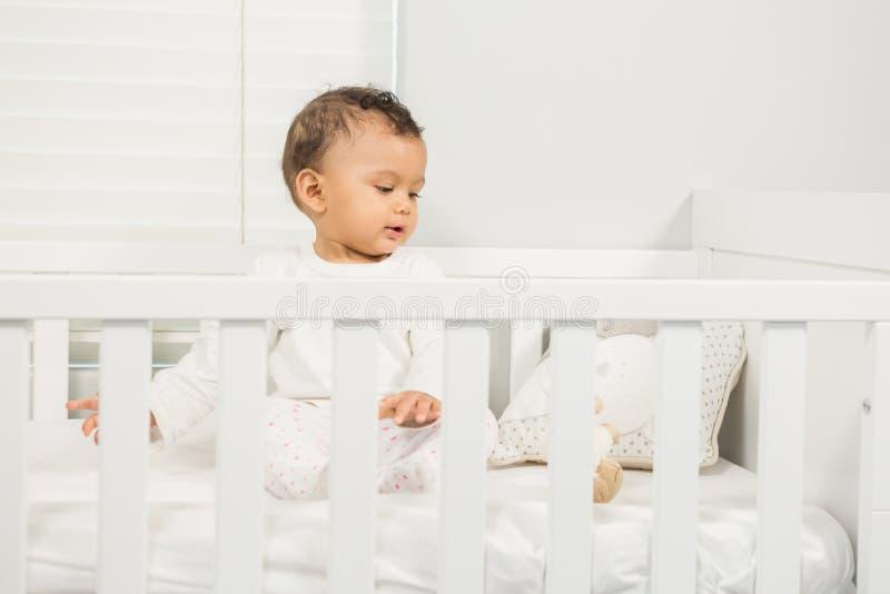Cute baby on crib. Cute baby sitting on the crib stock image