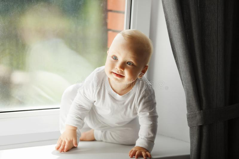 Cute baby with curious facial expression sits on windowsill. Cute baby with curious facial expression, big light eyes and blond hair in white crawlers, barefoot stock photos