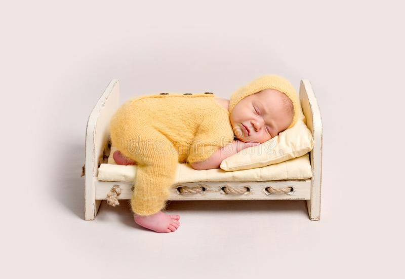 Baby dressed in knitted yellow costume sleeping on crib. Cute baby dressed in knitted yellow costume sleeping on small wooden crib with one leg on the floor stock photos