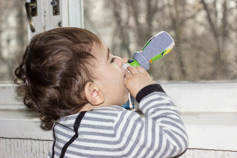 Cute baby drinking juice or yogurt from a bottle. Emotional portrait of a one-year-old child. stock photos