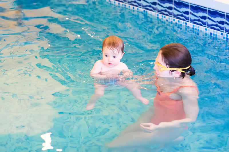 Cute baby in an early swimming class. Cute little baby in an early swimming class royalty free stock images