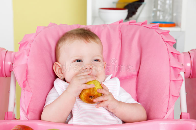 Cute baby eating fruit royalty free stock photos