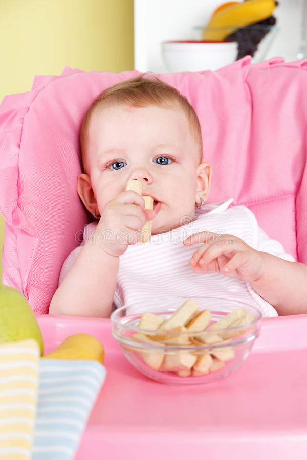 Cute baby eating snack royalty free stock images