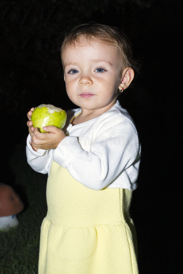 Cute baby eats yellow pear on black background stock photo