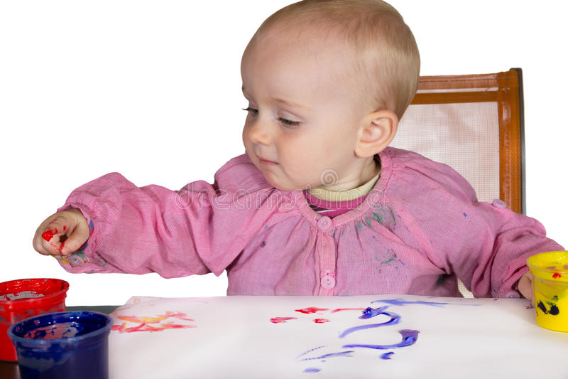 Cute baby experimanting with paint stock photo
