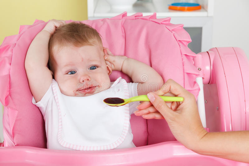 Cute baby is full of baby food royalty free stock photos