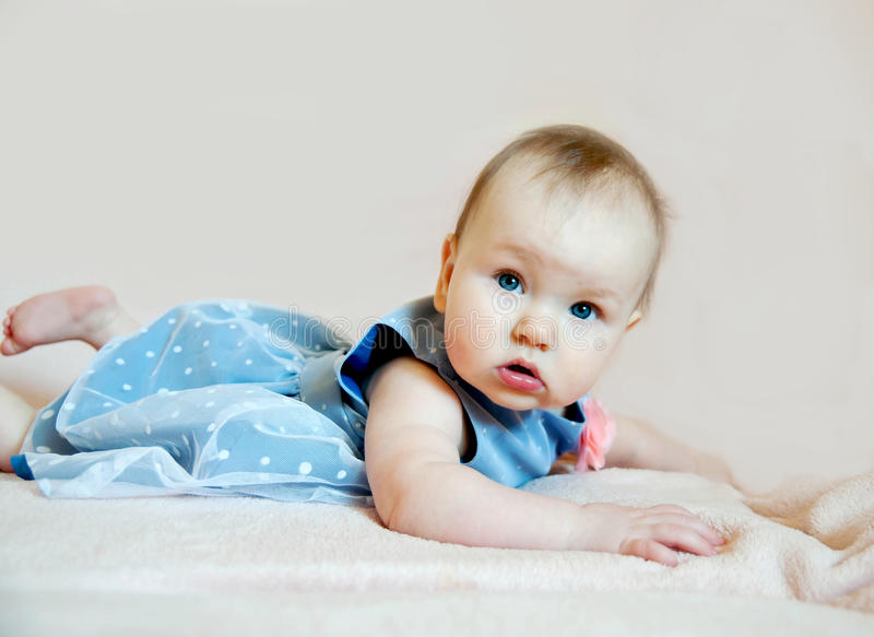 Cute baby girl in blue dress with pink flower royalty free stock photos