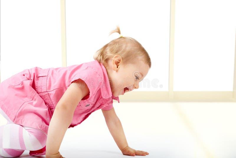 Cute baby girl crawling stock photo