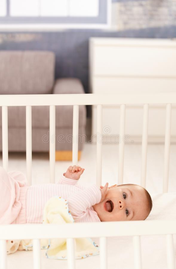 Cute baby girl in crib. Cute baby girl wearing pink lying in white crib royalty free stock photos