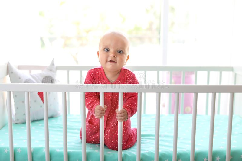 Cute baby girl in crib. At home royalty free stock photography