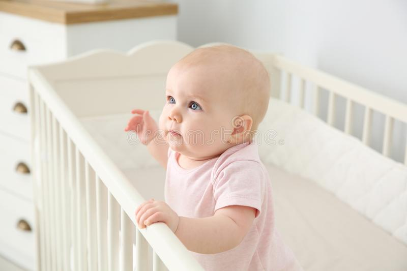 Cute baby girl in crib at home. Bedtime schedule stock image