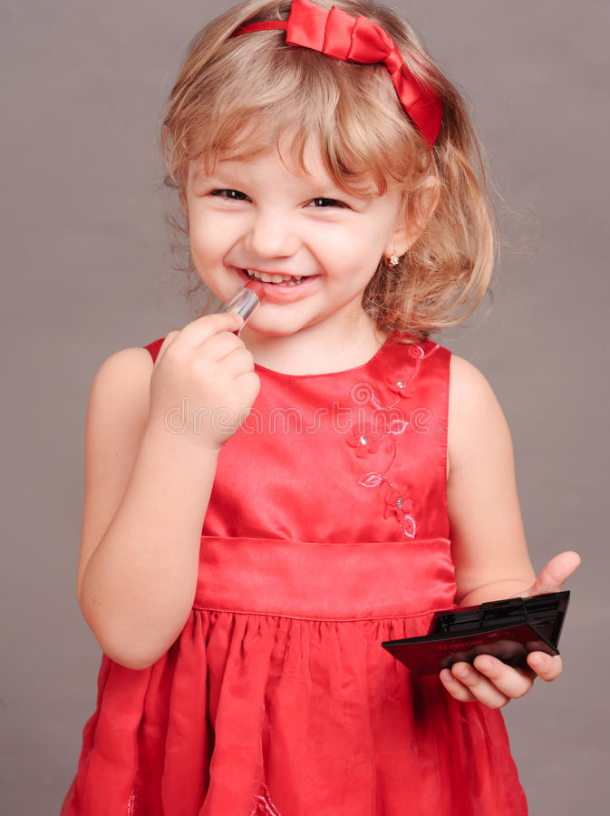 Cute baby girl doing makeup stock photography
