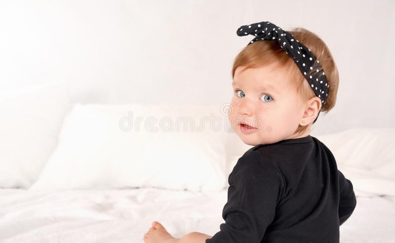 Cute baby girl dressed in a black dress on white bed background stock images