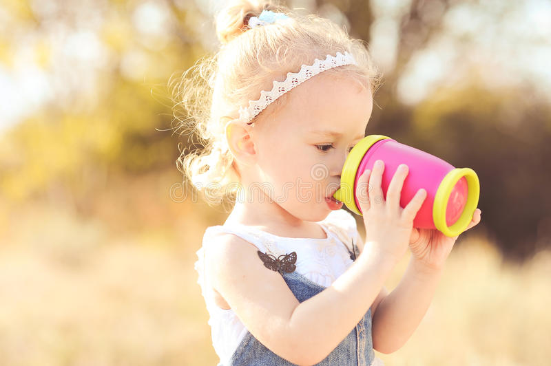 Cute baby girl drinking stock photography