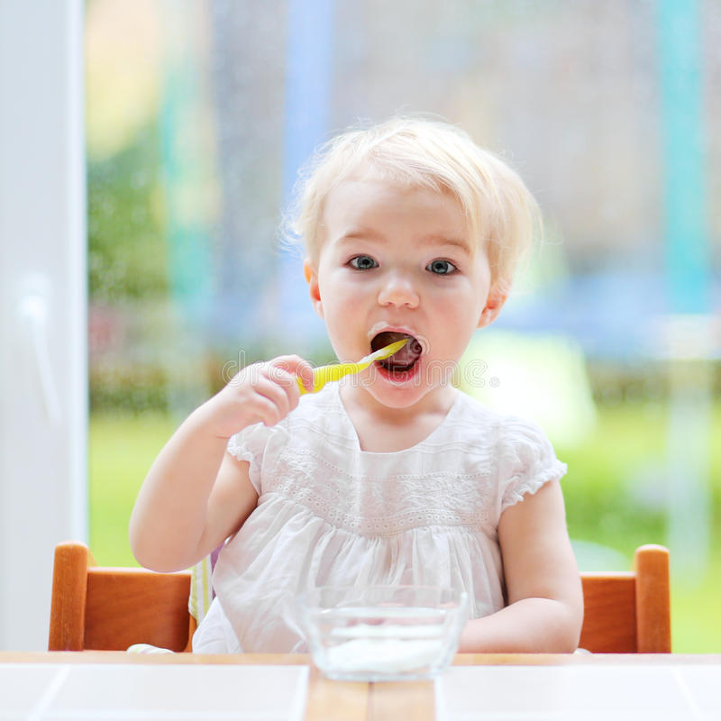 Cute baby girl eating yogurt from spoon. Smiling little child, blonde toddler girl eating delicious yogurt sitting in the kitchen in a high feeding chair next to royalty free stock image