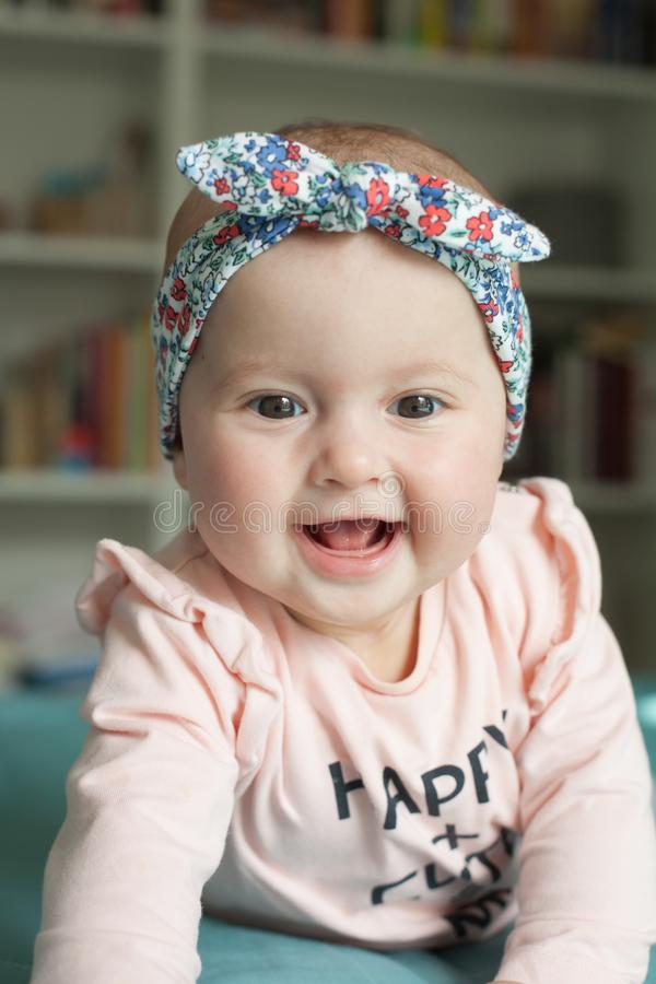 Cute baby girl with hairband ribbon, smiling, laughing. Adorable child having fun at home, happiness concept royalty free stock photography