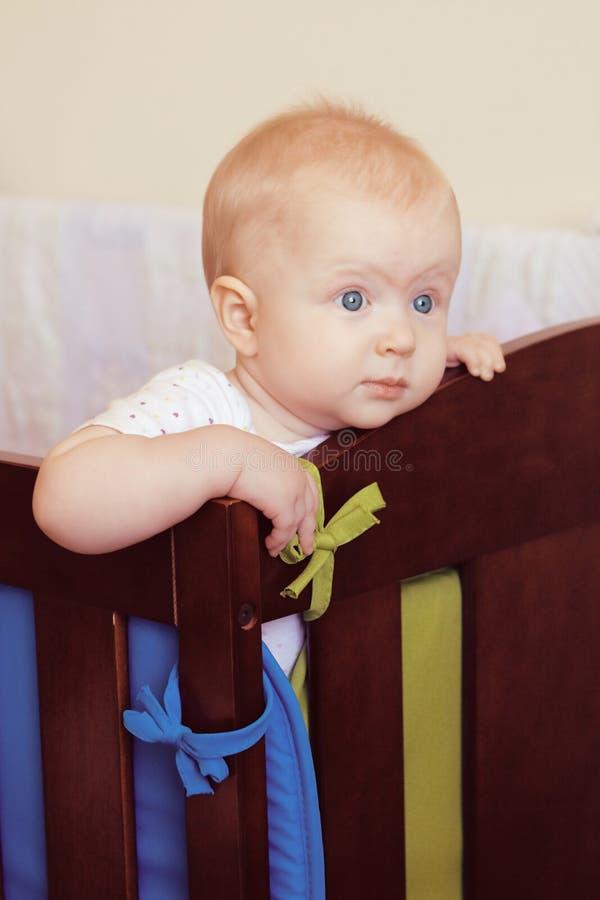 Cute baby girl in her crib stock photos