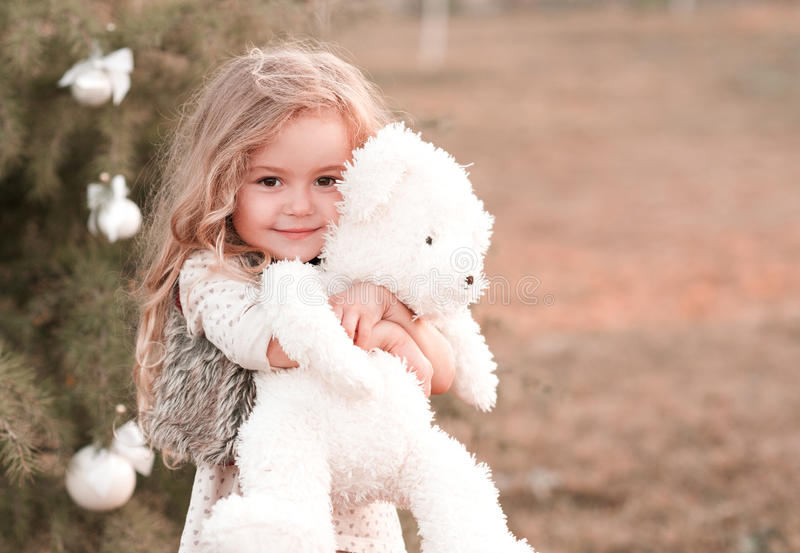Cute baby girl holding bear toy stock image