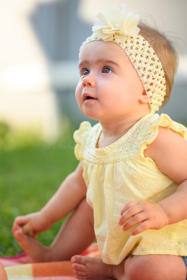 Free Cute Baby Girl In Yellow Band And Dress Sits In Sunny Backyard. 8 Months Old Infant Outdoors Royalty Free Stock Images - 162312479