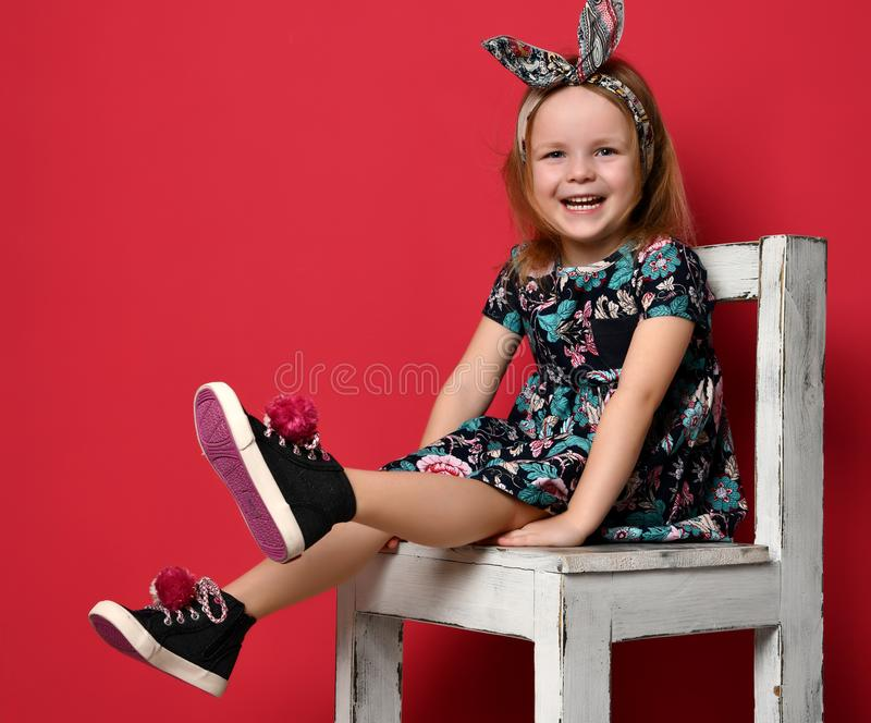 Cute baby girl kid in fashion summer dress and headband sitting on chair happy smiling stock images