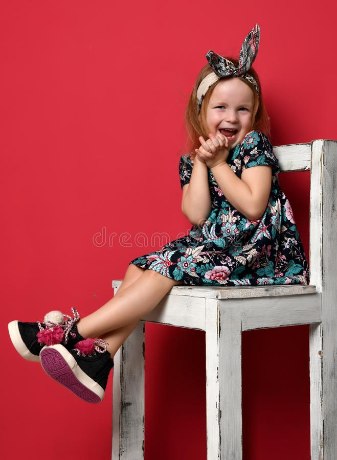 Cute baby girl kid in fashion summer dress and headband sitting on chair happy smiling royalty free stock photo