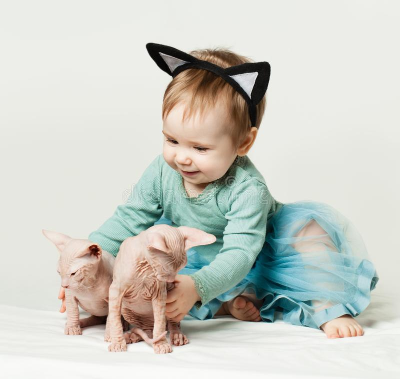 Cute baby girl with kittens stock photos