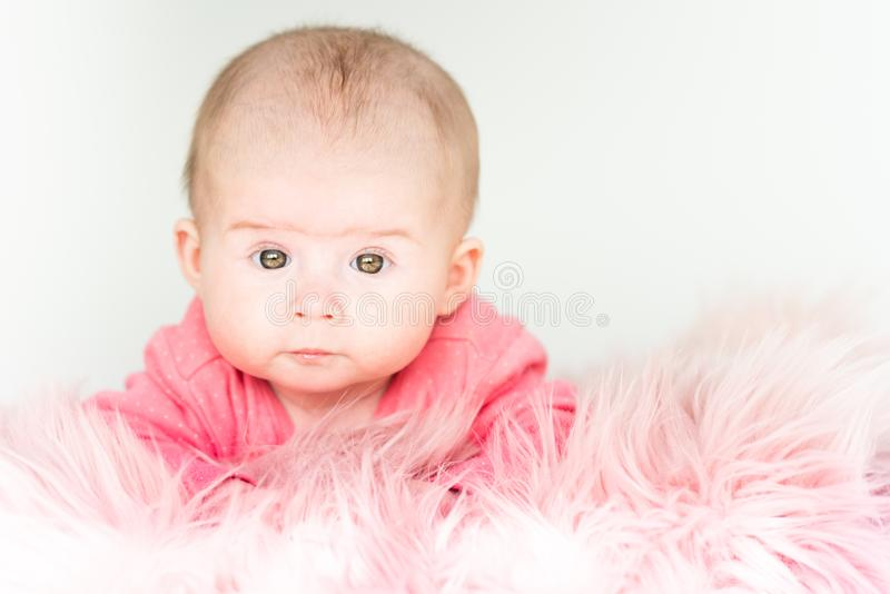 Cute baby girl lying on furry blanket on the bed at home and watching curiously. 4 month old baby stock photo