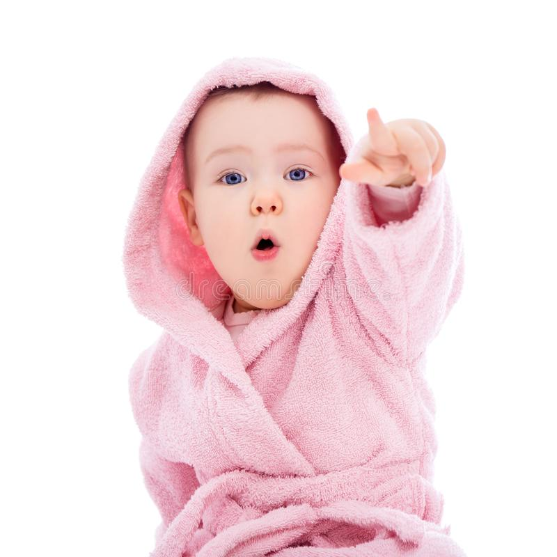 Cute baby girl in pink bathrobe pointing at something isolated on white. Background stock photo