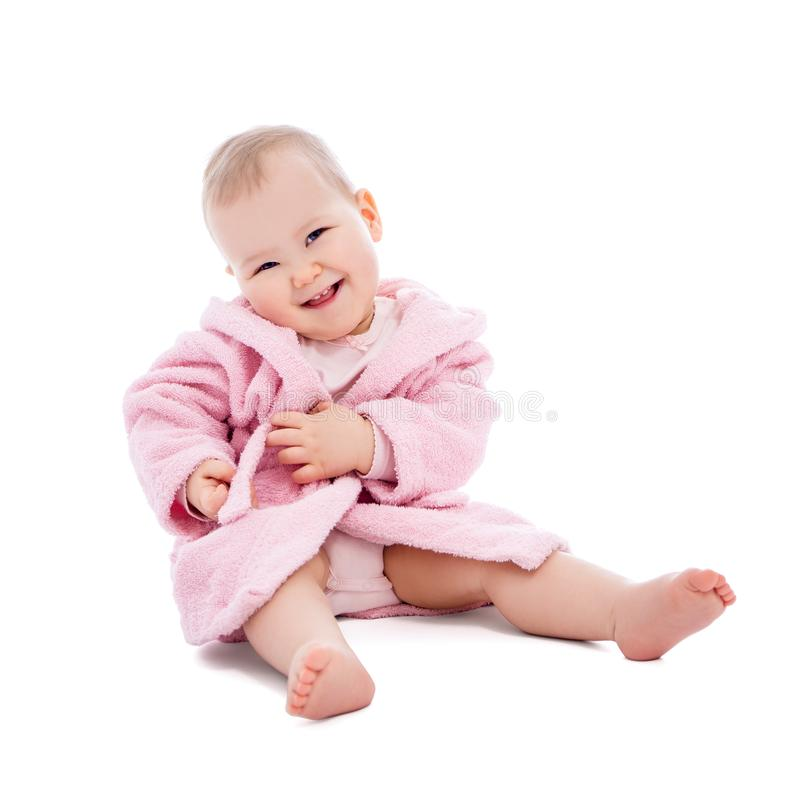 Cute baby girl in pink bathrobe sitting isolated on white. Background stock photography