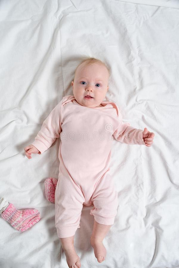 Cute baby girl in a pink suit smiling. Lying on a white sheet stock photos