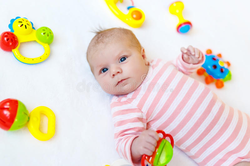 Cute baby girl playing with colorful rattle toys. Cute adorable newborn baby playing with lots of colorful rattle toys on white background. New born child stock photo