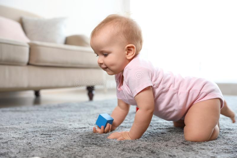 Cute baby girl playing on floor in room royalty free stock images