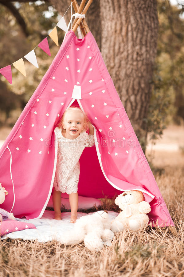 Cute baby girl playing outdoors. Laughing kid girl 1-2 year old playing in wigwam outdoors. Looking at camera. Childhood stock photo