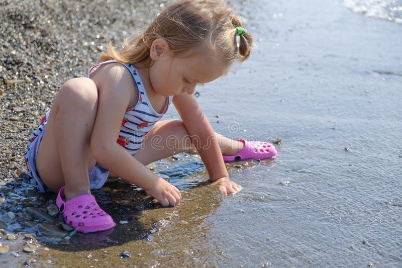 Cute baby girl is playing on sea cost with pebble, slow motion video stock photos